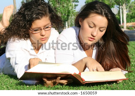2 young women laying in grass reading the bible