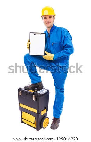 Young worker holding a blank clipboard with his foot on the toolbox against white - stock photo