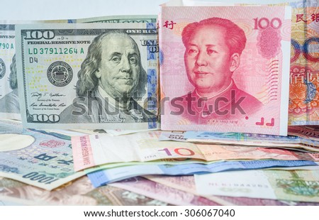 100 Yuan China currency banknotes and 100 US Dollar banknotes on a pile of international currencies banknotes - stock photo