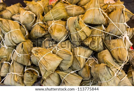Zongzi (pyramid-shaped dumplings made by wrapping glutinous rice in bamboo leaves) - stock photo