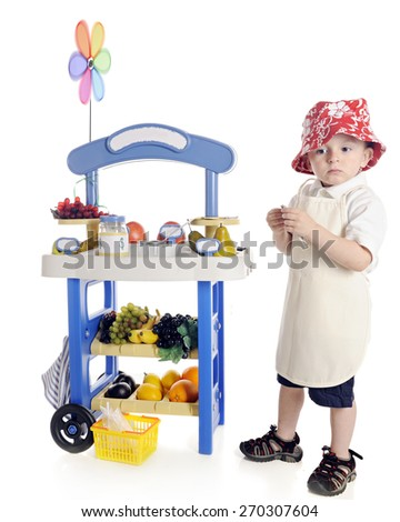 A adorable preschooler looking sad as he stands by his his fruit stand.  On a white background. - stock photo