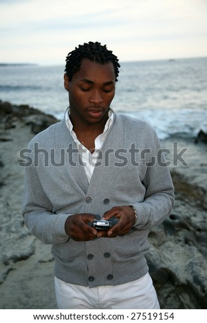 a african american man text messages outside on the beach - stock photo