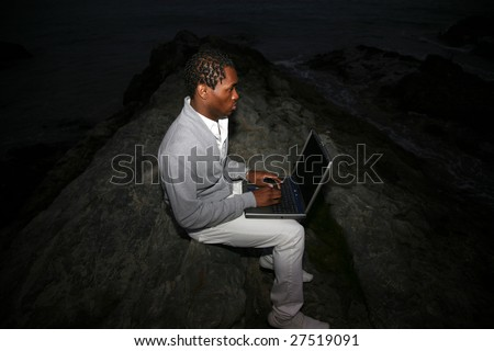 a african american man uses his laptop computer at night at the beach - stock photo