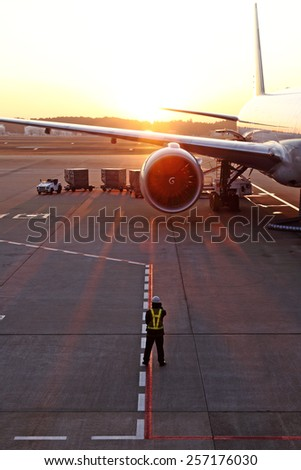 A airport traffic controller ground crew guiding an airplane on an airport runway against a fiery sunset.