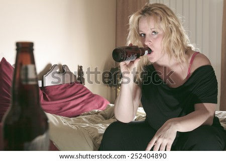 A alcoholic woman drinking beer in his bedroom. - stock photo