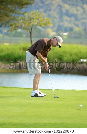 A amateur golfer competes on a 18 hole golf course - stock photo
