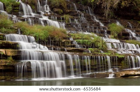 A amazingly beautiful series of cascades down a gorge wall. The water source is an underground cavern which pours the water out the side of the gorge wall. - stock photo