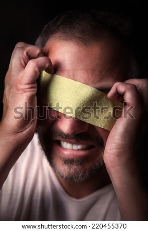 A angry blindfolded man wants to throw the tape away.Picture is toned - stock photo