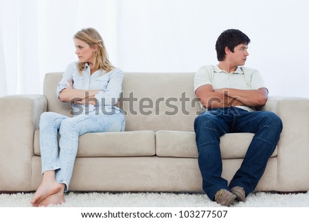 A angry couple sit at the two ends of the couch with their arms folded looking away