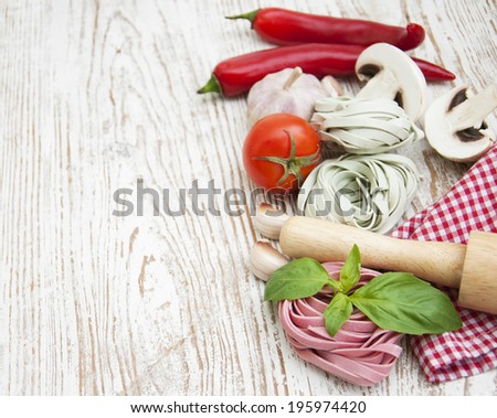 A arrangement of  pasta, garlic, tomatoes    on a wooden  background - stock photo