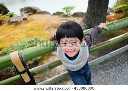 A asian boy playing outdoors evening time in the park, Japan