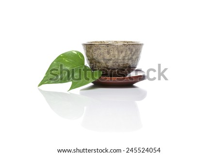 A asian(chinese) tea cup with leaf(leaves) isolated white at the studio. - stock photo