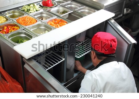 A Asian cook in a kitchen working on a vegetable buffet bar - stock photo