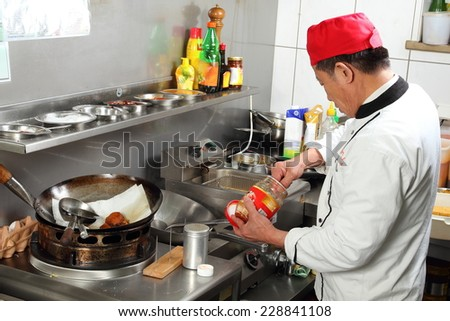 A Asian cook putting spices while cooking - stock photo