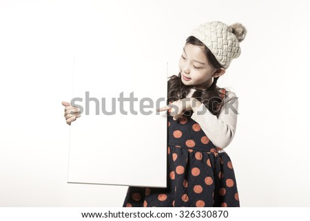 A asian(japan, chinese, korea) pretty girl hold a white(blink, empty) canvas frame with a smile isolated white at the studio. - stock photo