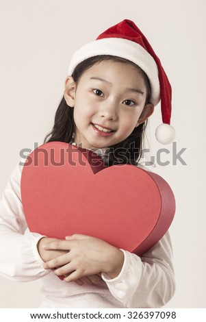 A asian(japanese, korean, chinese) girl(kid, children) hold a red heart(love) gift box for christmas(xmas) at the studio.
