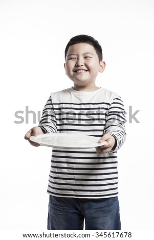 A asian(korean, japanese, chinese) boy(kid, child, man, male) make a pose with smile and hold a ceramic food tray for kids, baby isolated white. - stock photo