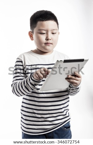A asian(korean, japanese, chinese) boy(kid, student, child, man, male) wearing white stripe shirts and blue denim hold and watch(see, touch) a digital device(pad, mobile, note) isolated white.