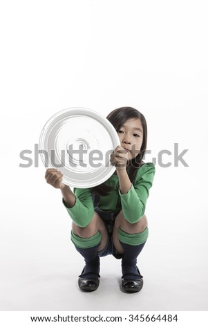 A asian(korean, japanese, chinese) girl(kid, child, woman, female) make a pose wearing green shirts, denim pants with smile and hold a ceramic white empty food tray for kids, baby isolated white.