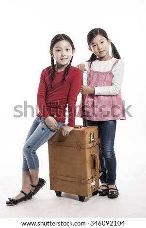 A asian(korean, japanese, chinese) girls(kid, student, child, woman, female) sit down and stand up with a luggage(suit case) for tour, journey isolated white.