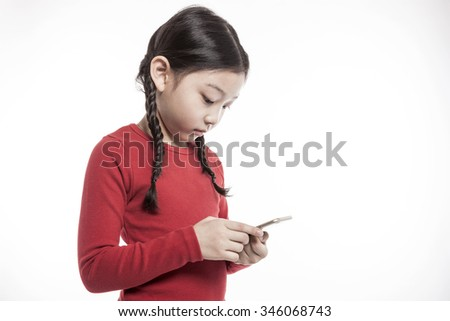 A asian(korean, japanese, chinese) girls(kid, student, child, woman, female) wearing red shirts and blue denim hold and watch(see), touch the screen a digital device(pad, mobile, note) isolated white.