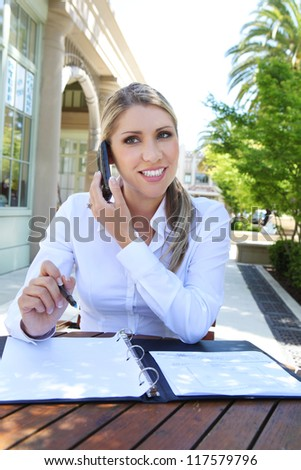 A attractive blonde business woman at office on the phone with notebook