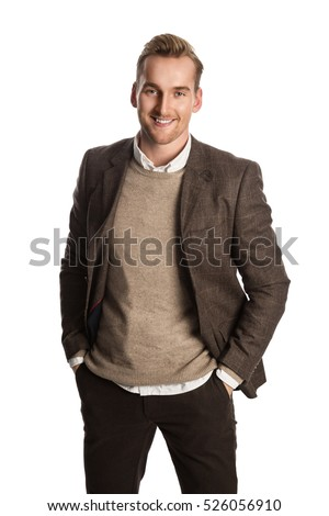 A attractive man in his 20s standing against a white background wearing a brown suit with a sweater and white shirt.