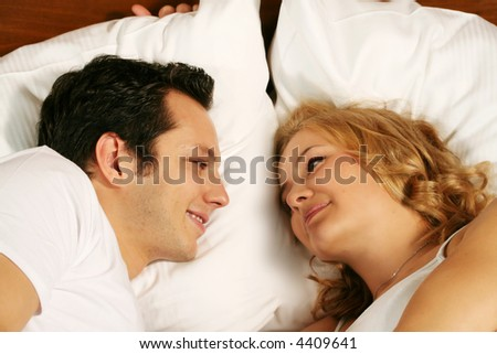 a attractive young couple is smiling in there bed at home