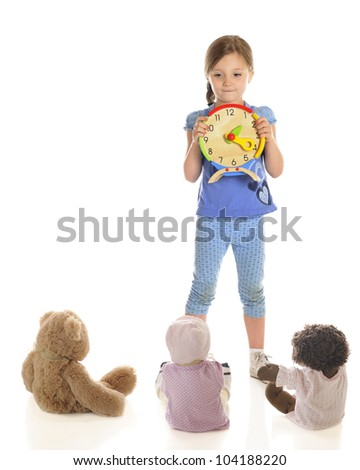 A attractive young elementary girl teaching her toys to tell time.  On a white background with plenty of space on the left for your text. - stock photo
