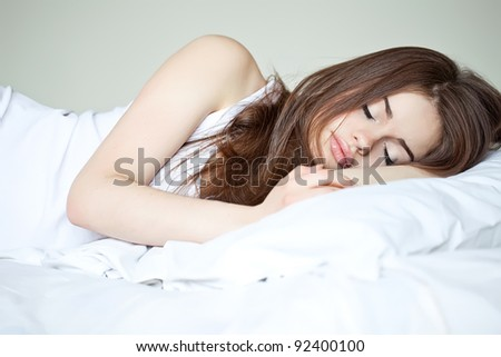 a attractive young woman is sleeping in her bed - stock photo