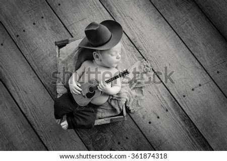 A b&w image of a three week old baby boy wearing a cowboy hat and jeans and playing a tiny acoustic guitar. He is lying in a wooden crate. Shot in the studio on a rustic, wood background. - stock photo