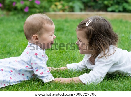 A baby and a toddler girl lying on the grass facing each other - stock photo