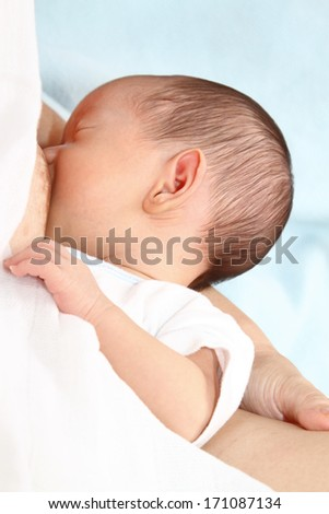 A baby boy being breastfed - stock photo