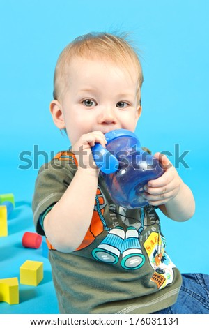 A baby boy holding a blue sippy cup. - stock photo