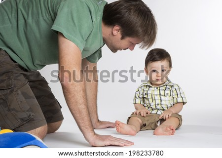 A baby boy sitting on a white background with his father.