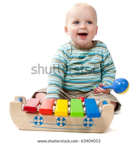 A baby boy with a big dribble playing with a rattle and a xylophone.  Isolated on white.
