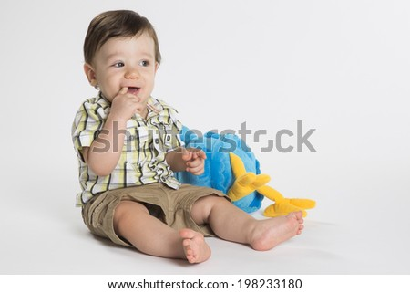 A baby boy with his toy on a white background