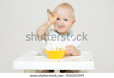 A baby eating food from a bowl against a isolated background. - stock photo