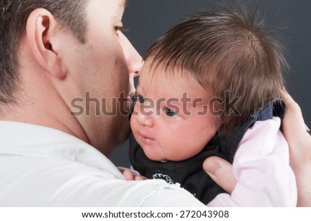 A baby girl enjoying a moment of cuddle with her dad - stock photo