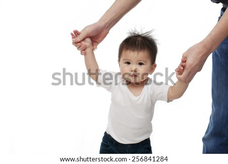 A baby girl is learning walking with the help of her parent, looking at the camera and smiling, isolated on white background - stock photo