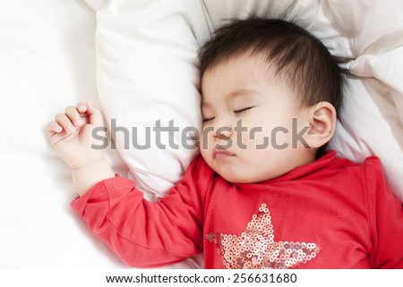 A baby girl is sleeping in red shirt, on a white bed sheet and blanket, on a white pillow, right hand making a fist, closeup - stock photo