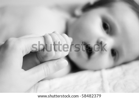 A baby holding a finger of his parents - shallow dof