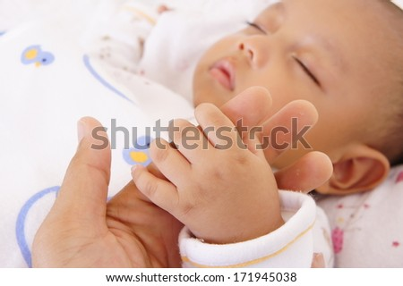 A baby holding his father's finger - stock photo