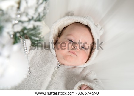 A baby in a white fur suit lies near the Christmas tree - stock photo