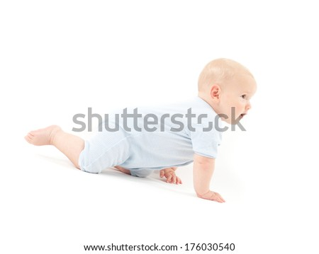 A baby in pale blue crawling on hands and knees.