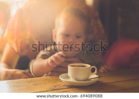 A baby is sitting at a table in a cafe and is reaching for his mother's cup of coffee