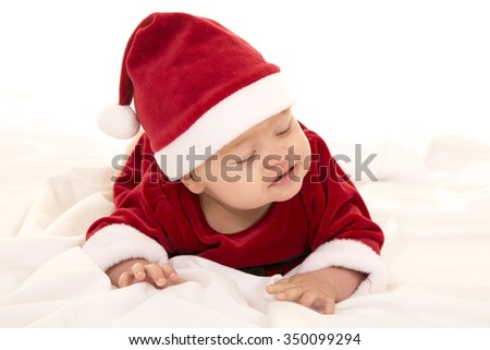 A baby laying on her belly in her Santa Costume, looking to the side. - stock photo