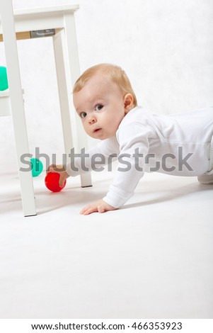 A baby of eight months old is making some activities on a gray background.
