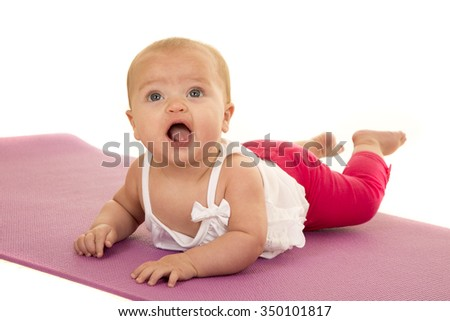 A baby on her belly on a fitness mat doing her yoga stretches.