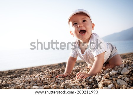 A baby playing at the beach. - stock photo